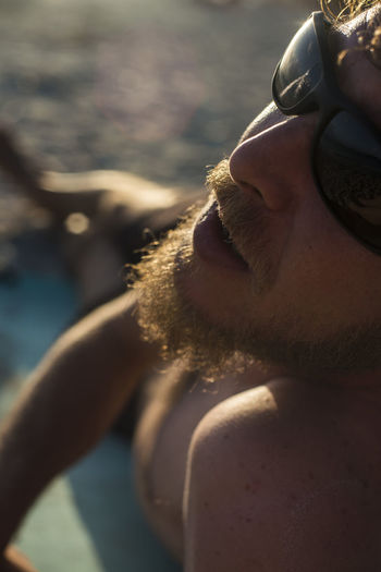 Close-up of man relaxing at beach