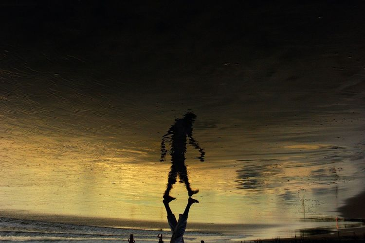 Upside Down Image Of Man Walking On Shore During Sunset