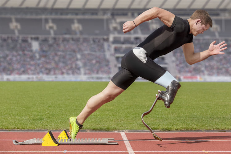 Male athlete with amputated leg on running on track