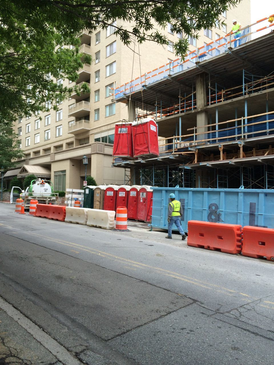Construction Worker Walking On Road By Building