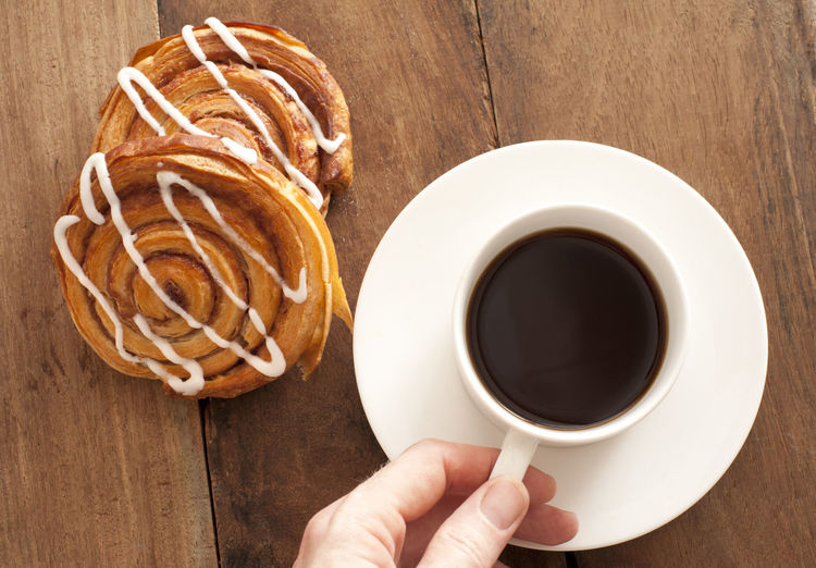 Man reaching for a cup and saucer of full roast espresso coffee with fresh Danish pastries for a refreshing coffee break, high angle view on wood Beverage Breakfast Bun Caffeinefood Coffee Coffee - Drink Coffee Break Coffee Cup Cup Danish Drink Espresso Food And Drink Hand Hot Pastry