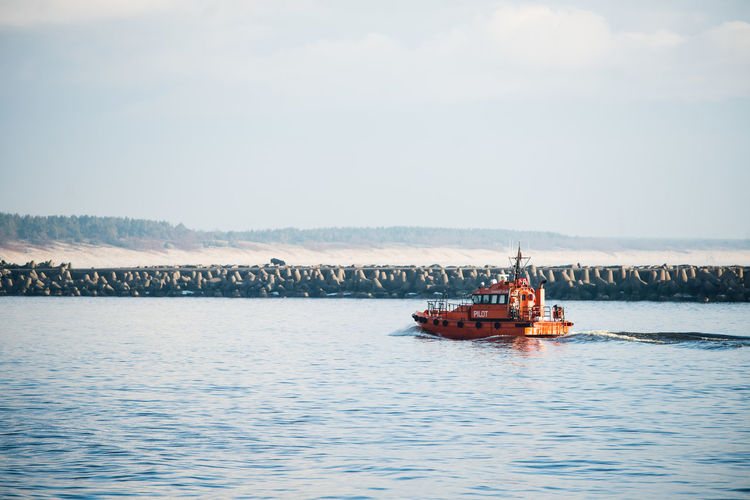 Trawler sailing in sea against sky