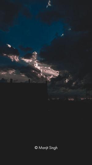 Silhouette people on illuminated street against sky at sunset