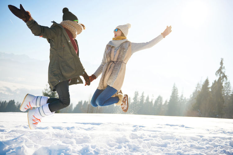 Happy woman jumping with arms raised over snow covered landscape against sky