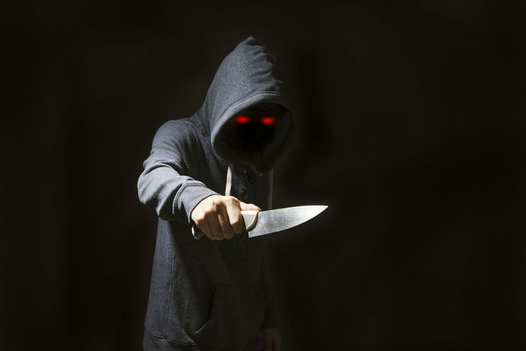 Thief holding knife against black background