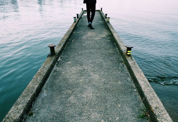 Low Section Of Man Walking On Pier