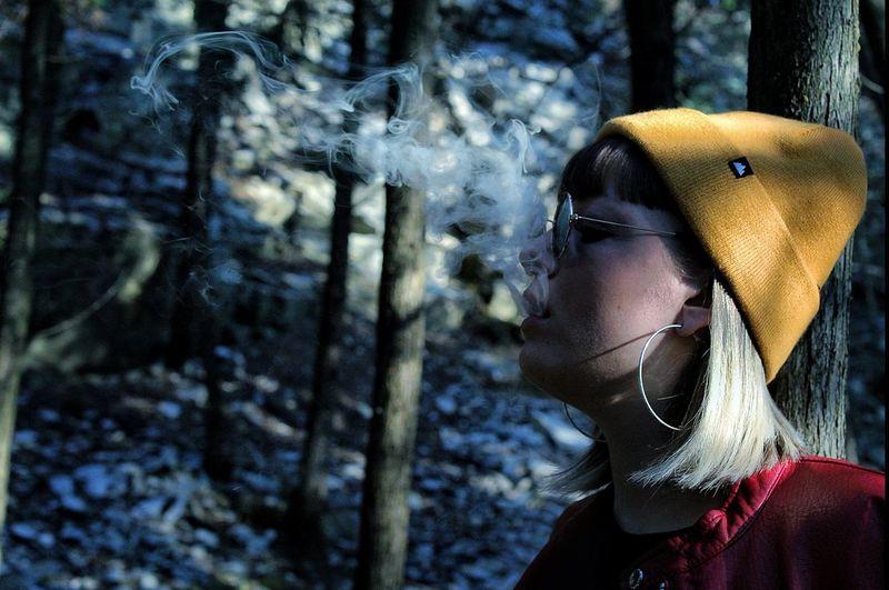 Woman exhaling smoke against tree