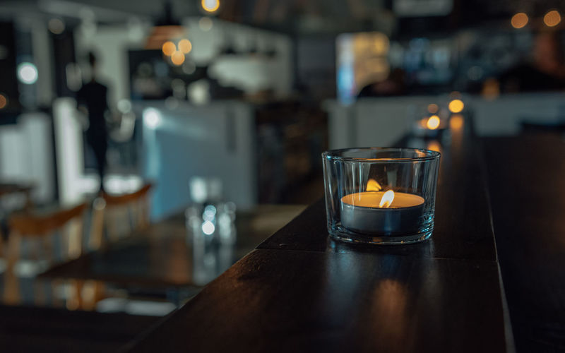Cosy café illuminated with old-fashioned light bulbs and candles Burning Candle Close-up Day Drink Drinking Glass Flame Focus On Foreground Food And Drink Freshness Illuminated Indoors  No People Refreshment Table