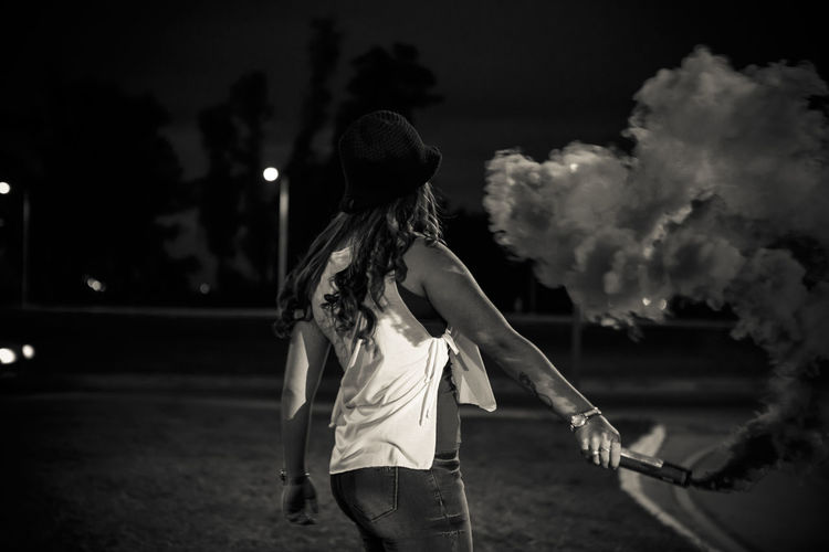 Rear view of woman holding distress flare on street at night