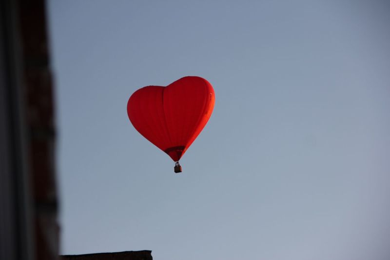 Low angle view of red heart shape hot air balloon flying in clear sky