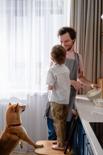 Family fun in the kitchen. cute little boy making whipped cream with his dad and furry friend