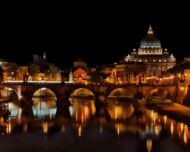Saint Angelo Bridge at night over the Tiber River with the St. Peter's Basilica in the background - Rome, Italy Architecture Bridge - Man Made Structure Building Exterior Built Structure Business Finance And Industry City Cityscape Dome Façade Gold Colored Government History Illuminated Night Outdoors Politics And Government Reflection Rome, Italy Scenics Sky St Peters Basilica Tower Travel Destinations Urban Skyline Water