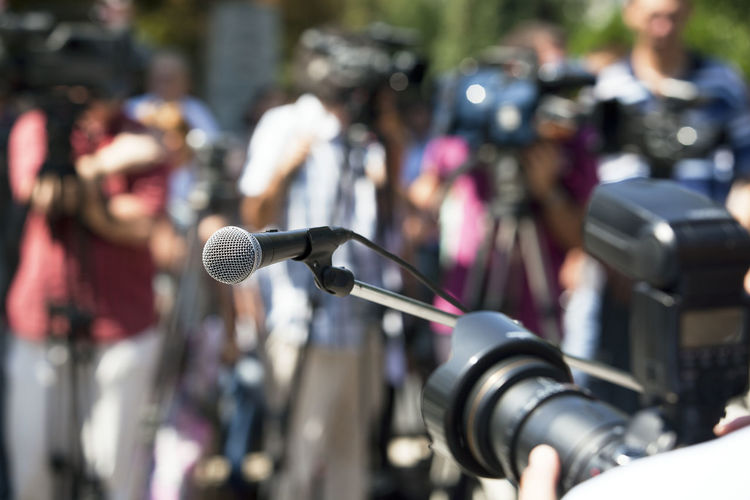 Close-Up Of Microphone Against Journalists