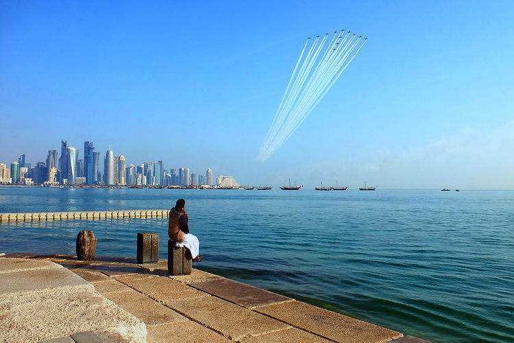 Man looking at air show while sitting on promenade by city against clear blue sky