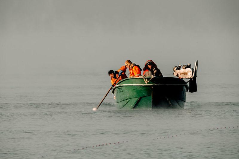 People in boat on sea against sky
