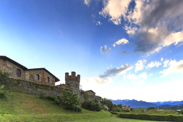 Candelo, Biella - May 4, 2016: Panoramic view of the Medieval village of Ricetto di Candelo in Piedmont, used as a refuge in times of attack during the Middle Age. Architecture Beauty In Nature Biella Blue Built Structure Candelo Candelo In Fiore Cloud Cloud - Sky Day Grass Hill Italy Landscape Medieval Village Mountain Nature No People Non-urban Scene Outdoors Ricetto Di Candelo  Scenics Sky Tranquil Scene Tranquility