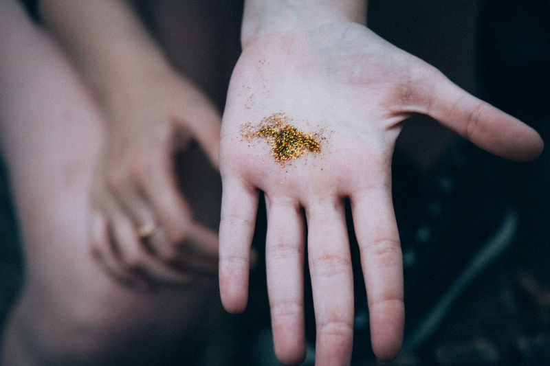 Midsection Of Woman With Golden Glitters On Palm