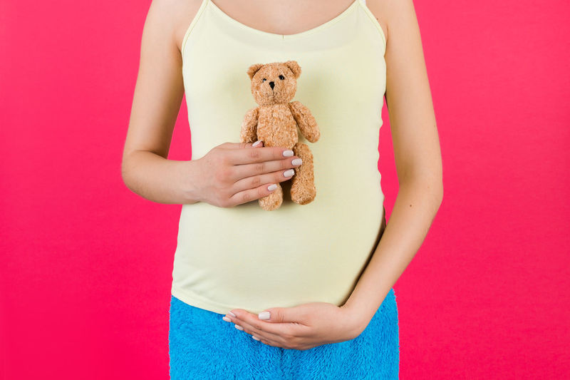Midsection of woman holding toy against pink background