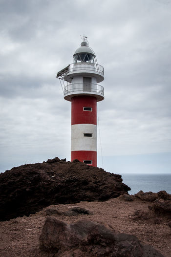 Lighthouse Punta Teno on Tenerife, Spain under a cloudy sky Punta Teno Architecture Building Building Exterior Built Structure Cloud - Sky Direction First Eyeem Photo Guidance Horizon Over Water Lighthouse Nature Protection Rock Rock - Object Safety Sea Security Sky Tower Water