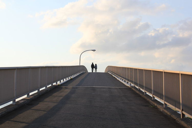 Rear View Of Friends Walking On Footbridge Against Sky