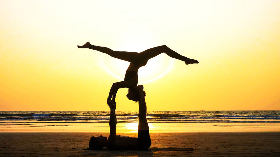 Silhouette man carrying woman while lying on beach against sky during sunset