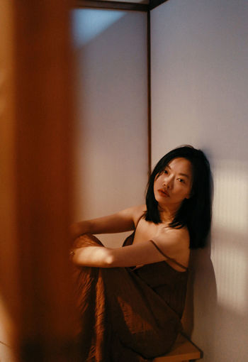 Portrait of a young woman sitting against wall at home
