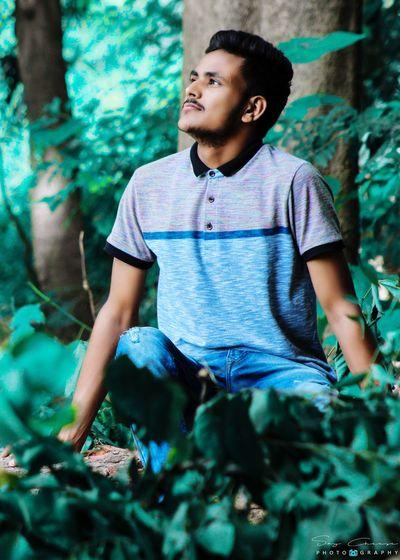 Boy looking away against plants