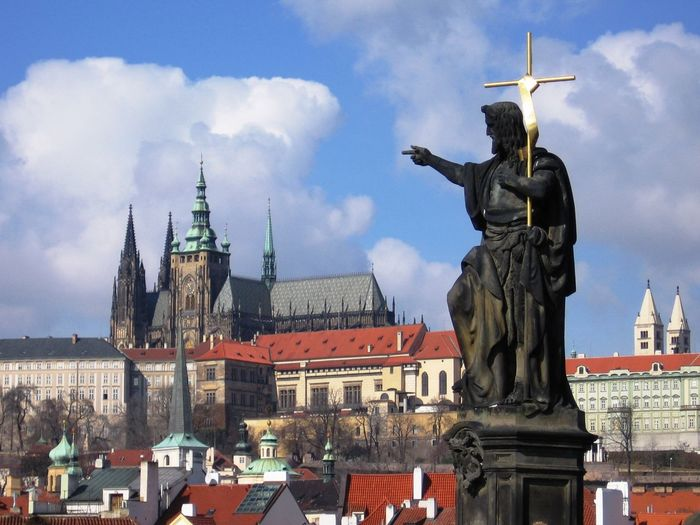 Saint Statue By St Vitus Cathedral With Cityscape Against Sky
