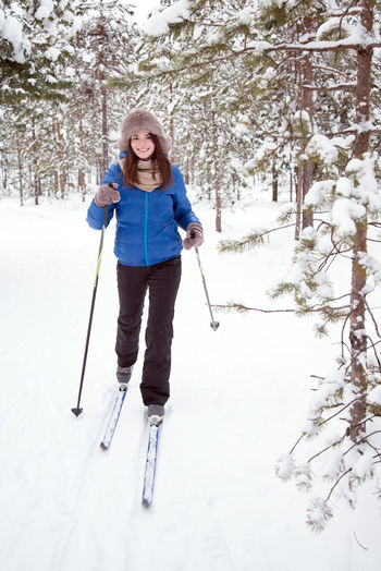 Full length of woman skiing on snow covered field