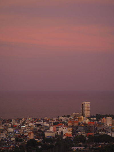 High angle view of townscape by sea against romantic sky