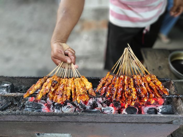 Low angle view of person preparing food on barbecue grill