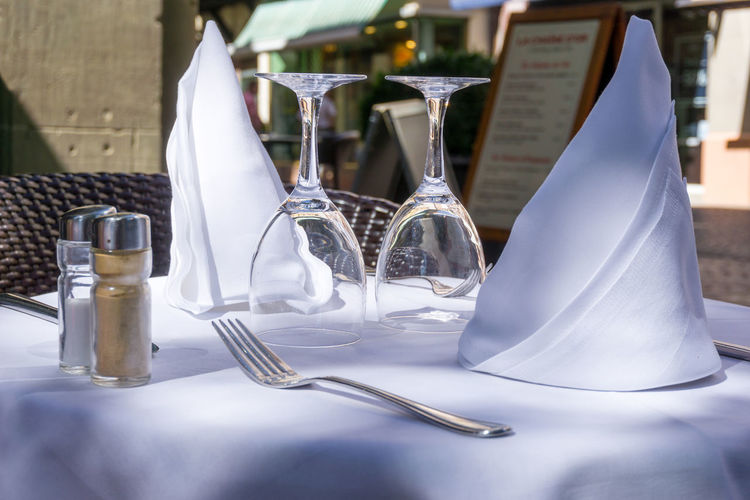 Close-up of wineglass with napkin on table at sidewalk cafe