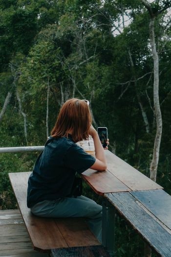 Woman using mobile phone while sitting on tree