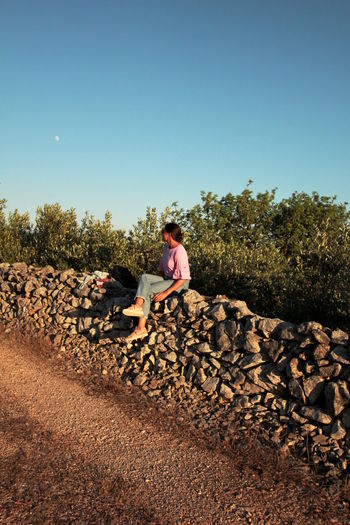 Woman sitting on stone wall against clear blue sky