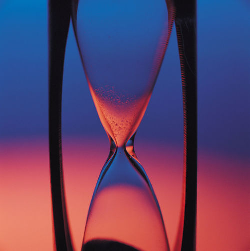Close-Up Of Hourglass Against Colored Background