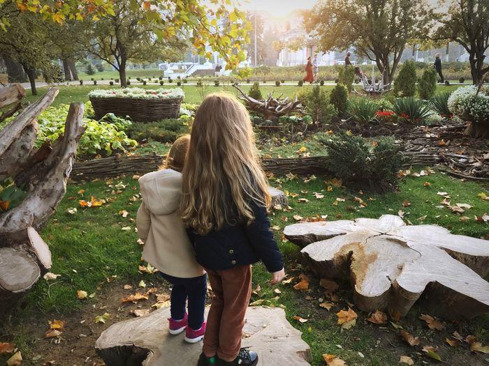 Rear view of siblings standing at park