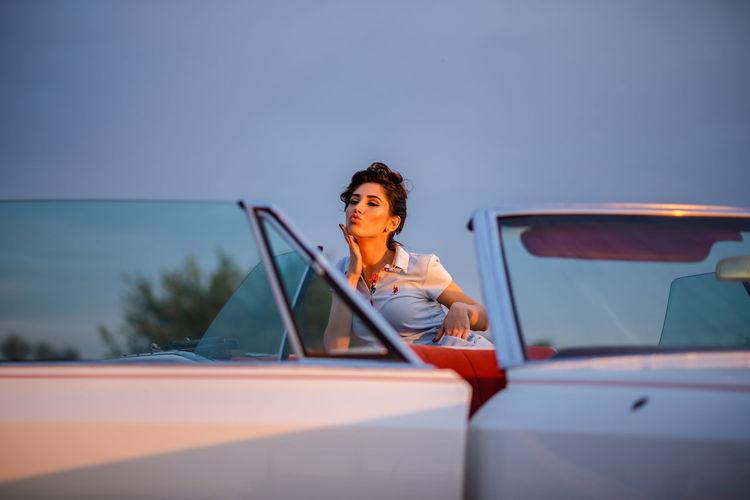 Portrait of woman sitting on car against sky