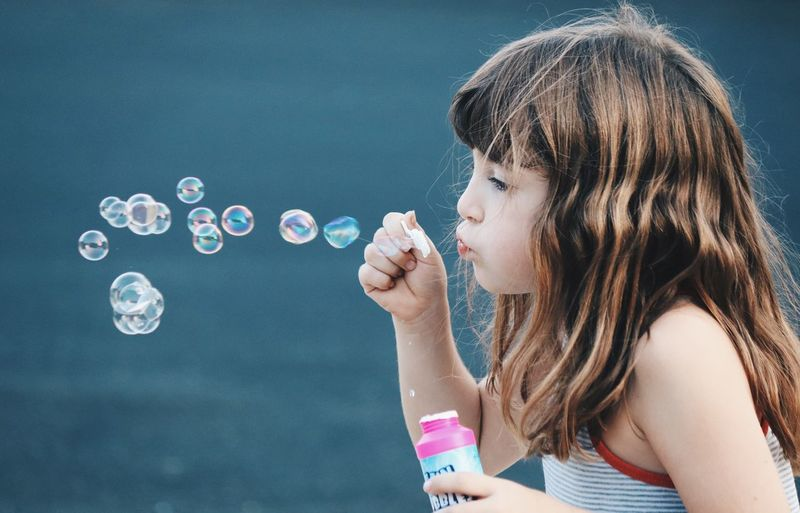 Side view of girl playing with bubble wand
