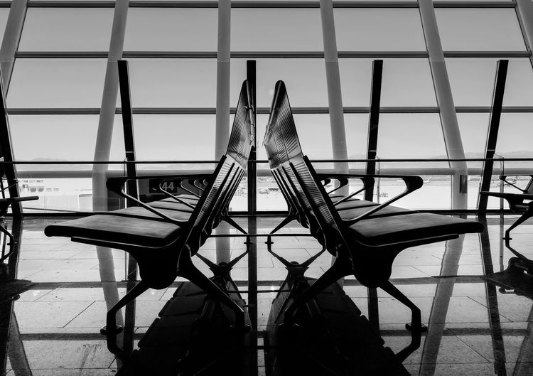 Empty seats on tiled floor against window at airport