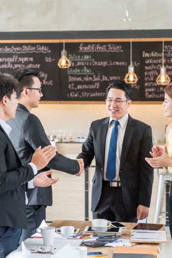 Business Businessman Cheerful Colleague Communication Cooperation Corporate Business Day Food And Drink Friendship Happiness Indoors  Meeting Men Mid Adult Men Partnership - Teamwork People Real People Smiling Suit Teamwork Togetherness Well-dressed Working