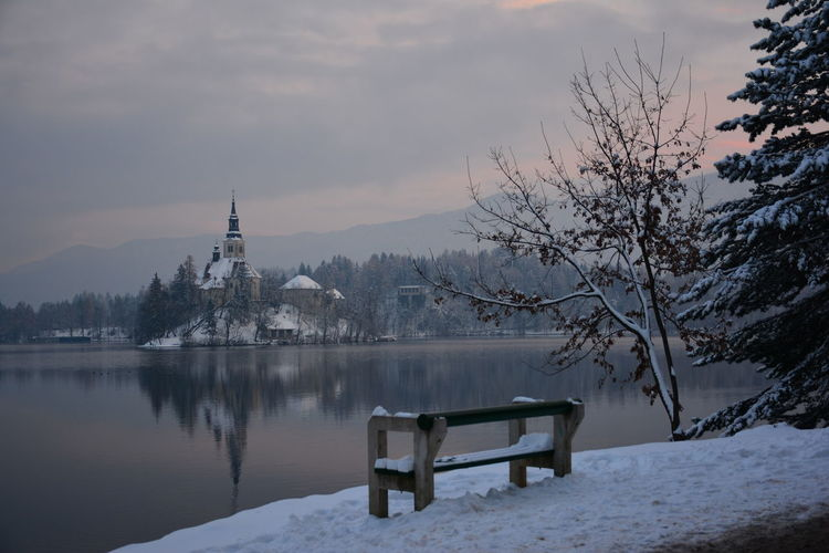 Empty bench by snowcapped mountain against sky during winter