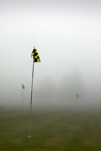 Yellow flag on field against sky