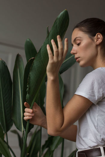 Side view of young woman holding plant