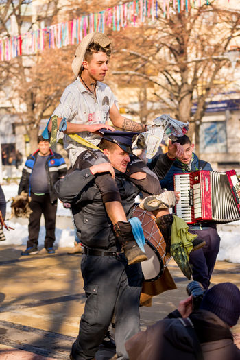 PERNIK, BULGARIA - JANUARY 26, 2018: Male dressed as policeman carries funny citizen with make-up in street festival at the annual International Festival of Masquerade Games Surva in Pernik, Bulgaria Bulgarian Culture Disguise Festival Season Pernik Policeman Adult Adults Only Bulgaria City Day Disguised Festival Holding Men One Person Outdoors People Real People Sitting Surva Women Young Adult
