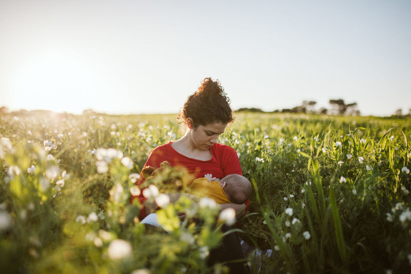 Mother feeding breast to daughter amidst plants against sky