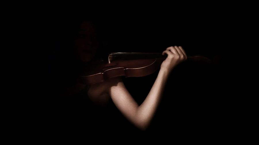 Woman Playing Violin Against Black Background