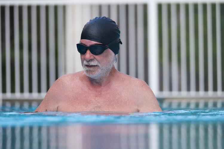 Portrait of senior man wearing sunglasses at swimming pool