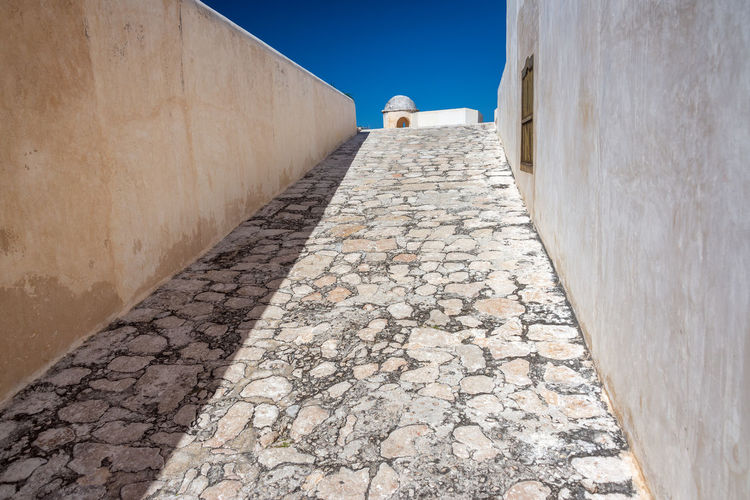 Empty footpath leading towards fort san miguel during sunny day