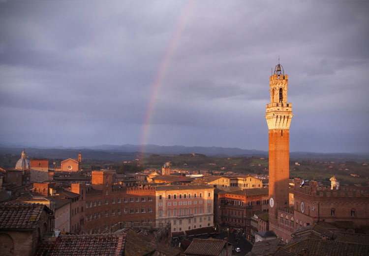 Siena (Italy): Torre del Mangia and Piazza del Campo at sunset with rainbow on background Siena Siena, Italy Italy Tuscany Rainbow Piazza Del Campo Piazza Del Campo Siena Piazza Del Campo. Siena Landmark Square City Cityscape Tower Sunset Medieval Architecture Medieval Travel Destinations Famous Places Building Exterior Architecture High Angle View No People Building Built Structure
