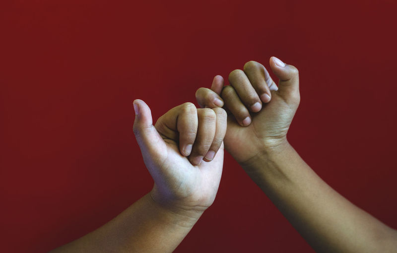 Close-up of man hand against red background